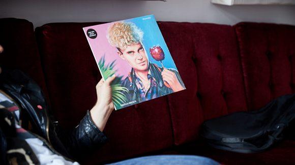 """Cover von Tristan Brusch Platte """"Das Paradies"""", auf dem er einen roten Liebesapfel hält."""