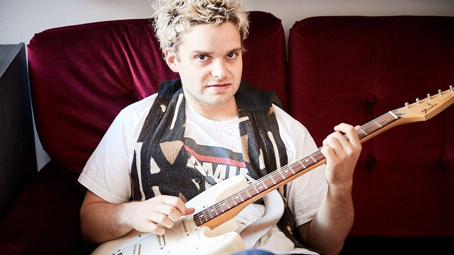 Der Musiker Tristan Brusch auf einem roten Sofa sitzend mit Gitarre in der Hand