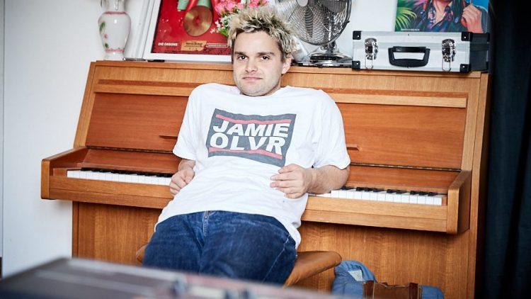 Tristan Brusch lehnt in seinem Studio mit den Armen auf einem Klavier