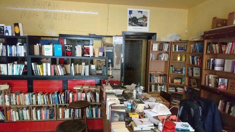 Buchladen mit Schreibtisch und gebrauchten Büchern auf gebrauchten Regalen