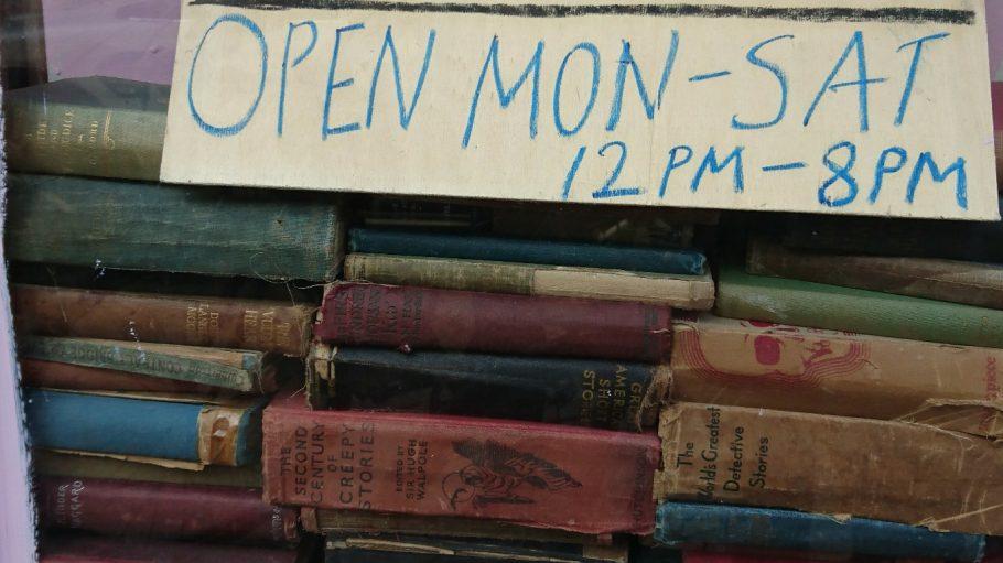 Alte englische Second Hand-Bücher in einem Schaufenster mit selbst geschriebenem Pappschild mit Öffnungszeiten