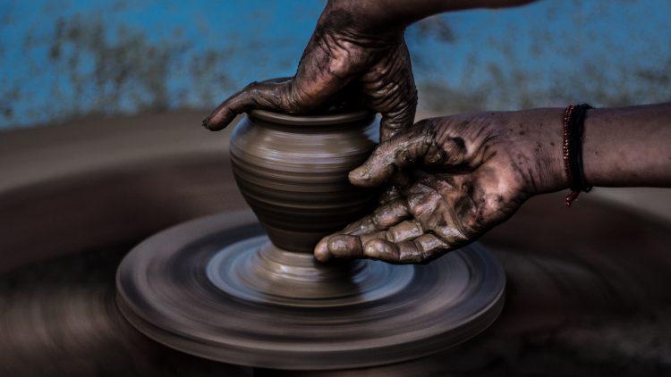 Zwei lehmverschmierte Frauenhände halten eine Vase auf einer Töpfer-Drehscheibe