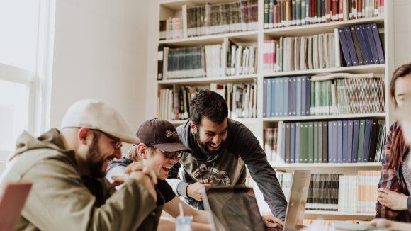 Drei junge Männer lachen während sie in einen Laptop schauen. Im Hintergrund ein Bücherregal