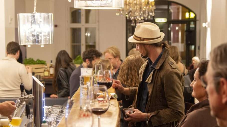 Menschen bei Eröffnung des Cafés beim Trinken an der Bar.