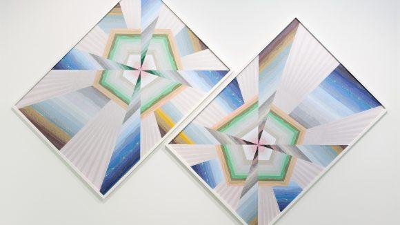 Zwei geometrische Bilder, die schief hängen. Von Haegue Yang mit dem Titel Trustworthy.