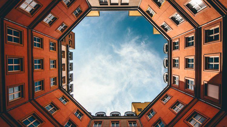 Blick nach oben in den Himmel aus einem Innenhof