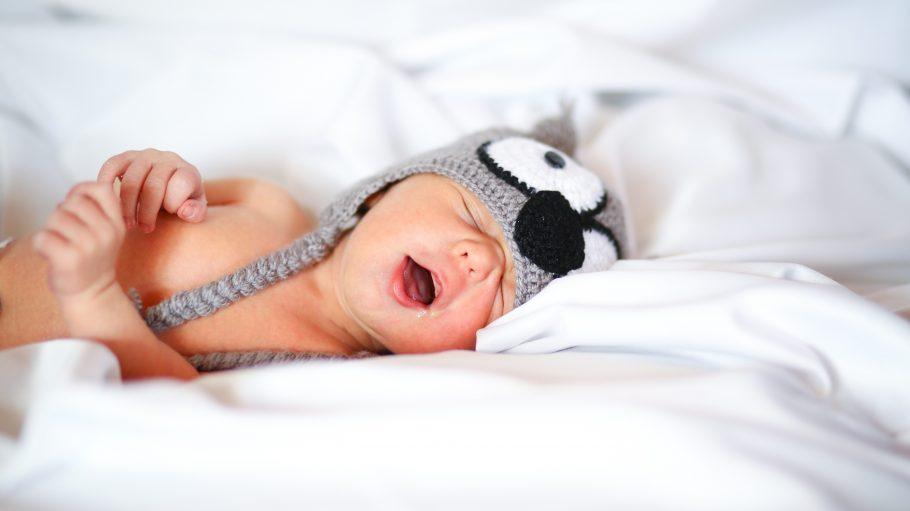 Baby mit Strickmütze Koala-Strickmütze liegt auf einem Bett mit weißer Decke