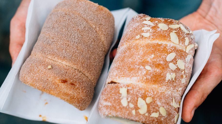 Mensch, der zwei Stücke Baumkuchen mit Zimt und Zucker und Mandeln in den Händen