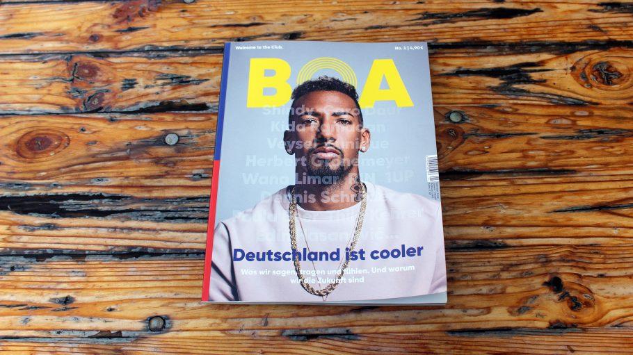 Holztisch mit Zeitschrift Boa, auf deren Titelbild Jerome Boateng, Mann mit weißem Pullover und Goldkette abgebildet ist.