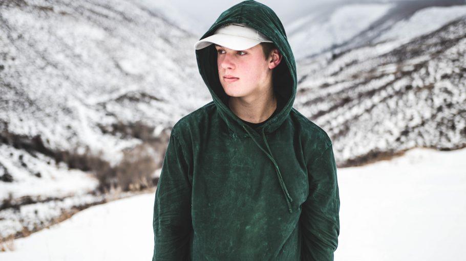 Junger Mann steht in Schneelandschaft, Cap und Hoodie auf dem Kopf
