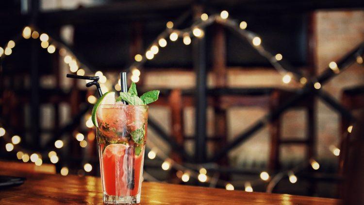 Roter Cocktail mit Limette auf Holztisch, dahinter Lichterkette.