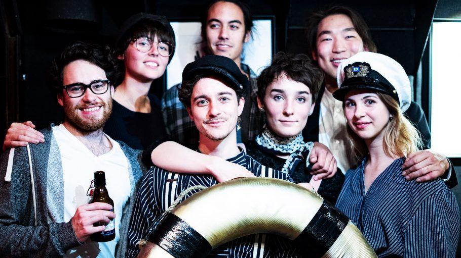 Vier junge Männer und drei junge Frauen stehen hinter einem goldenen Rettungsring