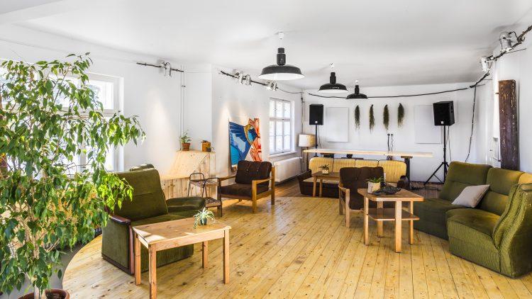 Sessel aus Holz mit braunem und grünem Polster, dazu Holztische auf Holzboden.