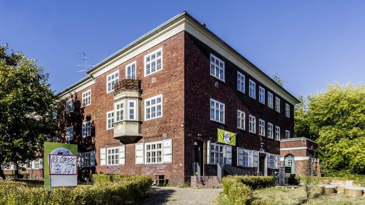 """Backsteinhaus der Gaswerksiedlung Berlin mit gelbem Transparent über der Tür, auf dem """"Flow"""" steht"""