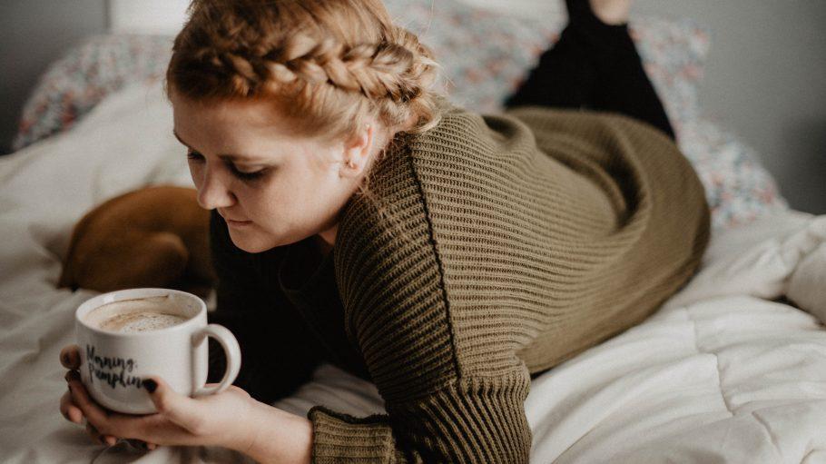 Frau mit großer Tasse in der Hand liegt auf einem Bett