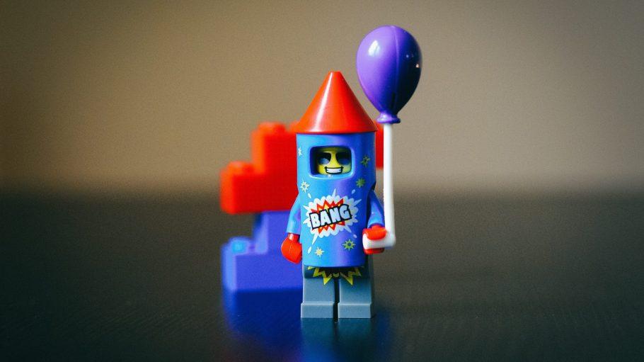 Legomännchen mit Raketenkostüm und einem Luftballon in der Hand.