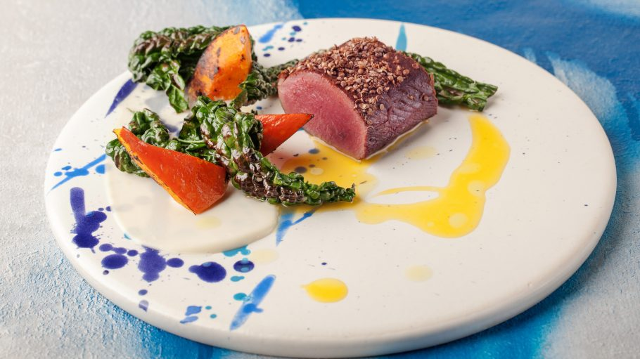 Ein Stück Hirsch mit Rübe auf einem bunten, kunstvollen Teller.