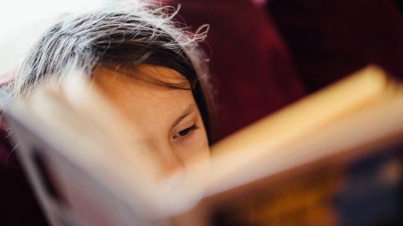 Gesichtshälfte eines Mädchens auf einem roten Sofa, hinter unscharfem Buch