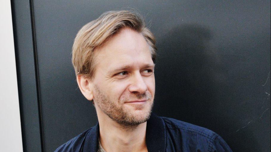 Matthias Lier Porträtbild: Schauspieler mit blonden Haaren und Dreitagebart, blaue offene Jacke, darunter grauer Pullover, schaut leicht nach rechts und lächelt