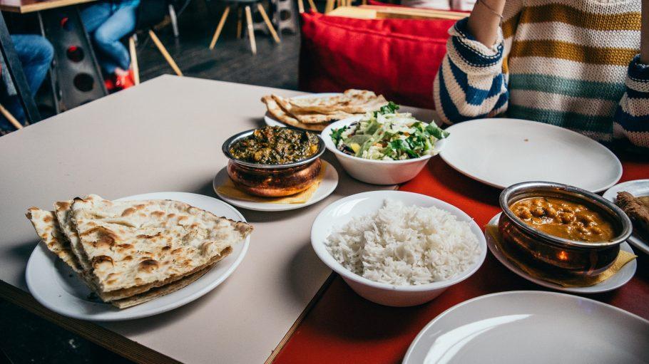 Tisch in einem Restaurant mit indischen Gerichten drauf.