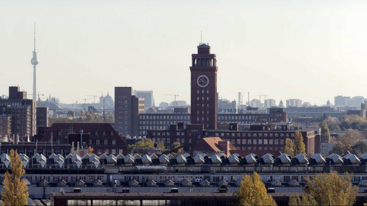 Skyline von Berlin-Siemensstadt mit rotbraunem Uhrenturm und Werksgebäuden unter blauem Himmel, links im Hintergrund der Fernsehturm am Alexanderplatz