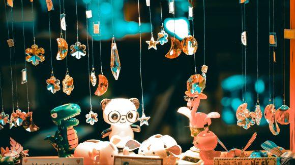 Schaufenster mit Glasschmuck an Schnüren, einem Spielzeugdrachen und Panda