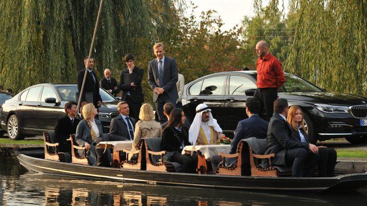 Ein mit Frauen und Männern im Business-Outfit sowie einem Scheich besetzter Kahn auf einem Kanal im Spreewald, dahinter Autos, Bäume und weitere Männer, in der Mitte Matthias Lier