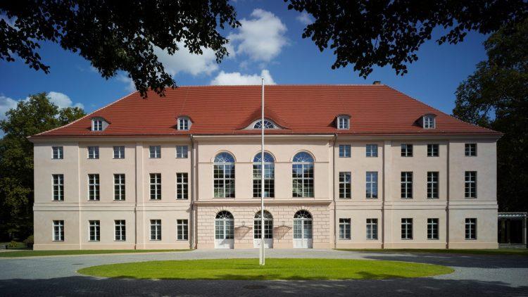 Schloss Schönhausen, beige mit rotem Ziegeldach, davor eine Zufahrt, Wiese und ein Fahnenmast ohne Fahne