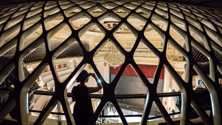 Hinter einer gitterartigen Kuppel steht eine Frau mit Hut, die in den Opernsaal der Staatsoper Unter den Linden schaut