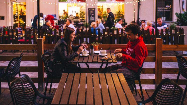 Junge Frau mit langen Haaren und junger Mann in rotem Hoodie sitzen draußen an Cafétisch, im Hintergrund andere Gäste