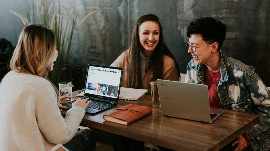 Zwei junge Frauen und ein junger Mann sitzen an einem Holztisch im Café mit zwei offenen Notebooks und Getränken