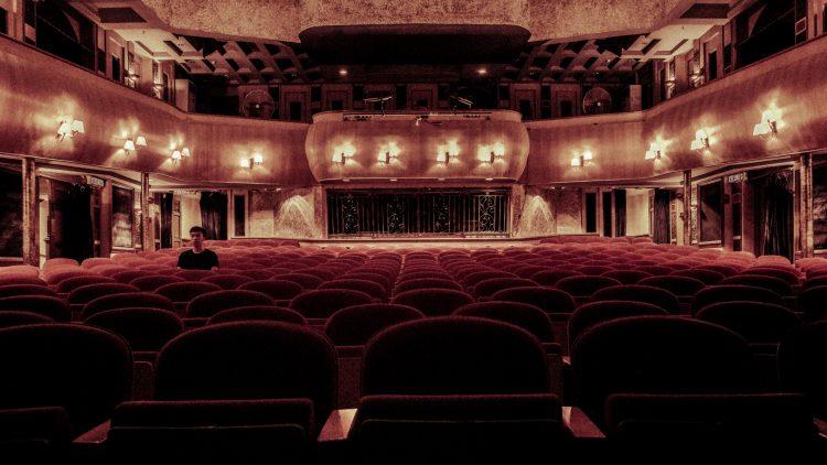 Theatersaal mit roten Sitzen, in dem nur ein Mann mit schwarzem T-Shirt sitzt