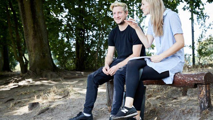 Musiker Teesy und QIEZ-Redakteurin im Interview am Seeufer unter Laubbäumen auf einer Bank.