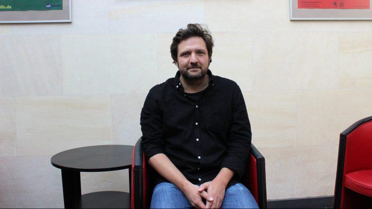 35-jähriger Mann mit Bart, braunen Haaren, dunkelblauem Hemd und Jeans sitzt auf Sessel neben kleinem Tisch