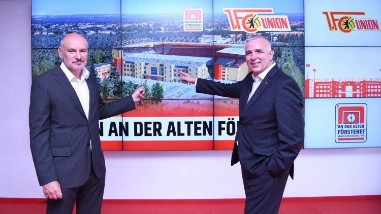 Zwei Männer in Anzügen (Dirk Thieme und Dirk Zingler) zeigen auf eine Bildschirmwand mit dem Bild des neuen Stadions an der Alten Försterei von Union Berlin