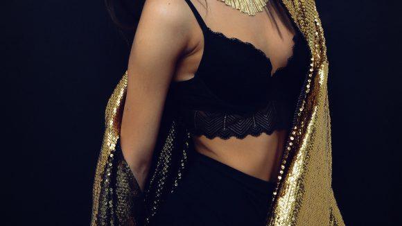 Eine Frau in schwarzen Dessous und goldenem Ummhang