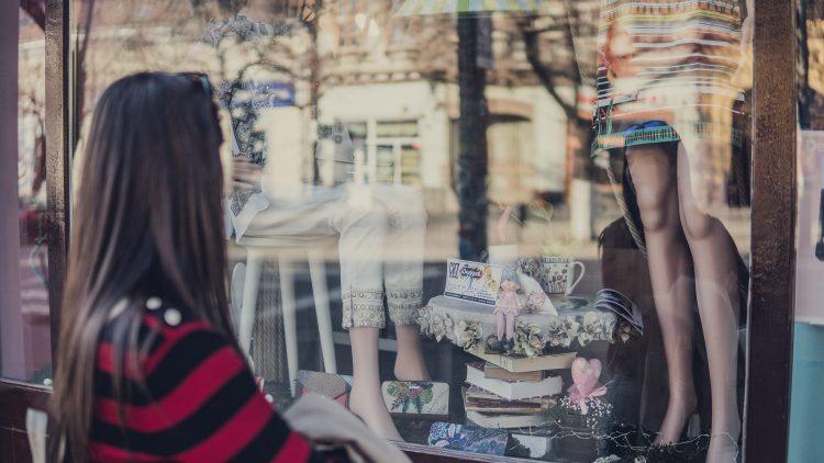 Frau mit braunen Haaren steht vor einem Schaufenster