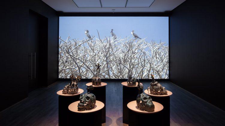 Künstlerische Totem-Köpfe in einem Kreis angeordnet. Dahinter eine Leinwand mit Vögeln, die auf Bäumen sitzen.