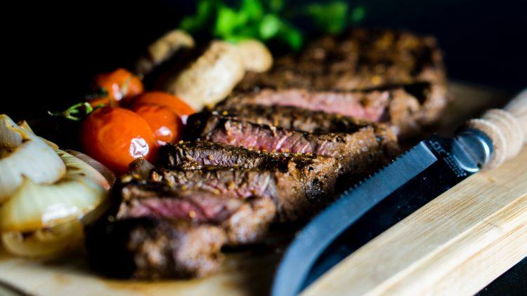 Geschnittenes Steak mit Gemüse auf einem Holzbrett.