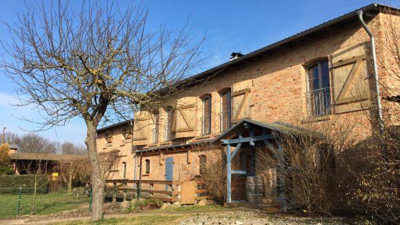 Haus aus Backstein mit blauen Holzelementen