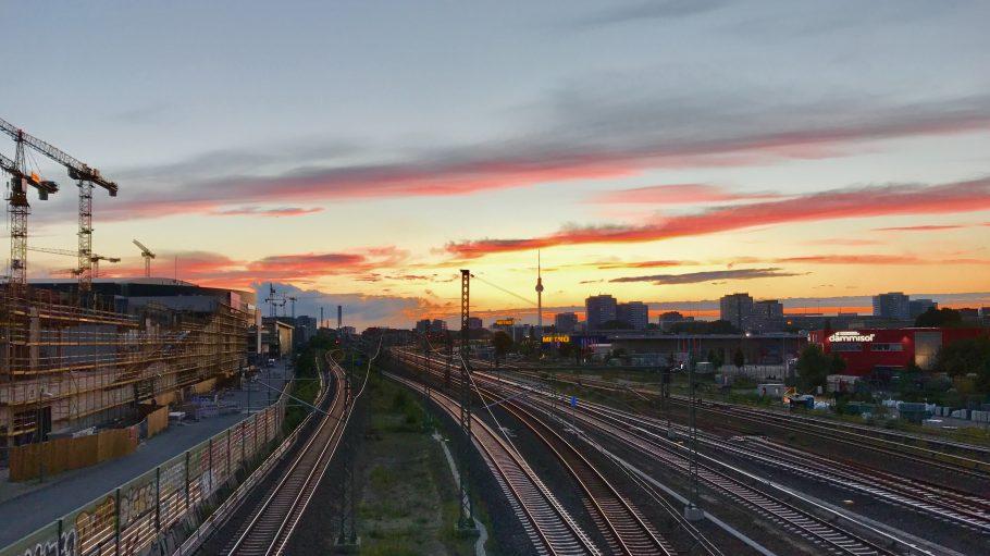 Bahngleise bei Sonnenuntergang: Blick von Osten mit eingerüstetem Haus links, Berliner Fernsehturm im Hintergrund