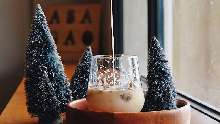 Cocktailglas zwischen Deko-tannenbäumchen mit Schneespitzen