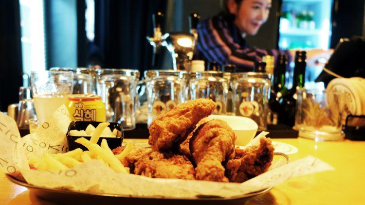 Platte mit frittierten Hähnchenflügeln und Pommes, dahinter koreanische Limo-Dose und Gläser, dahinter Zapfhahn und junge Frau