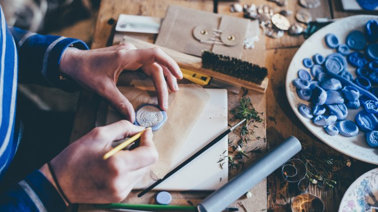 Menschenhand fertigt Wachssiegel an.