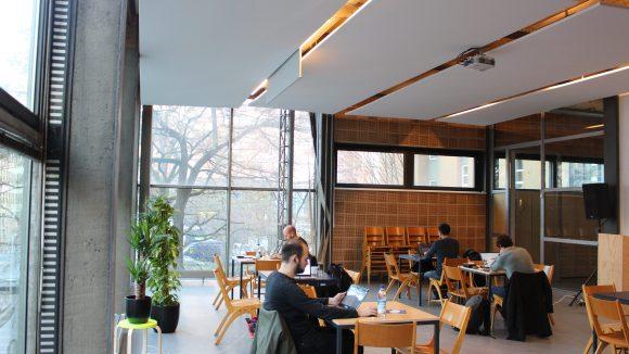 Leute arbeiten an Holztischen und mit Kaffee im Betahaus.