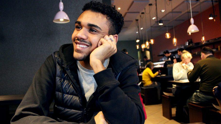 Langston Uibel an einem Tisch im Restaurant Kuchis in Berlin, lachend.
