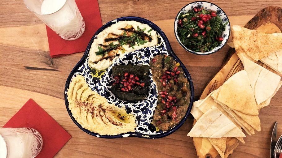 Ein bunter Teller mit verschiedenen Pasten, Salat und Pita-Brot. Daneben zwei Gläser mit Ayran.