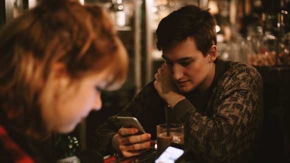 Junger Mann schaut in einem Café auf sein Smartphome