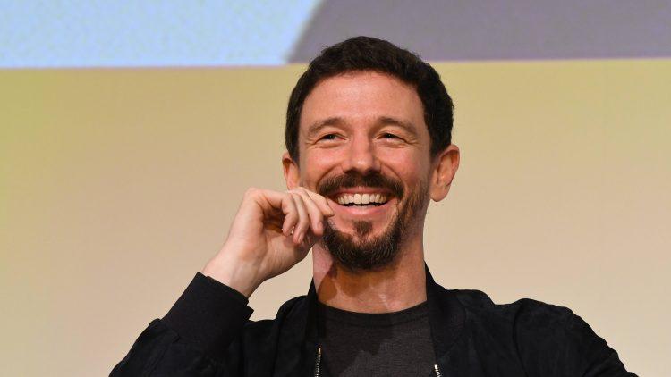Lächelnder Mann mit dunklen Haaren und kurzem Bart hält Hand an Kinn, schwarze Jacke geöffnet