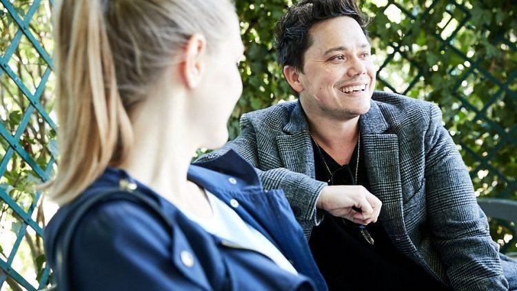 Patric Scott und eine blonde QIEZ-Redakteurin lachen gemeinsam auf einer Bank am Savignyplatz.